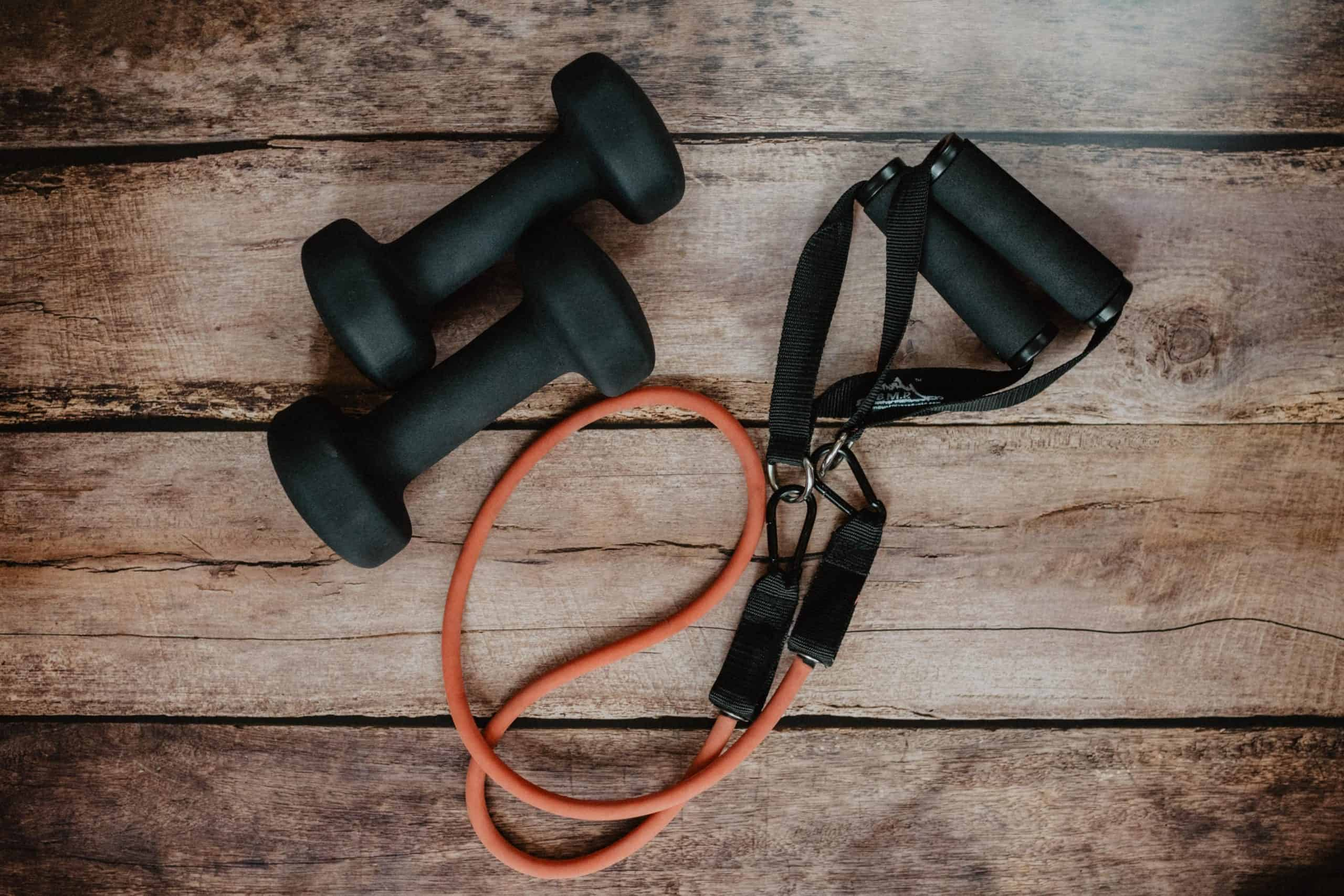 black hand weights and a resistance band against a wooden board background