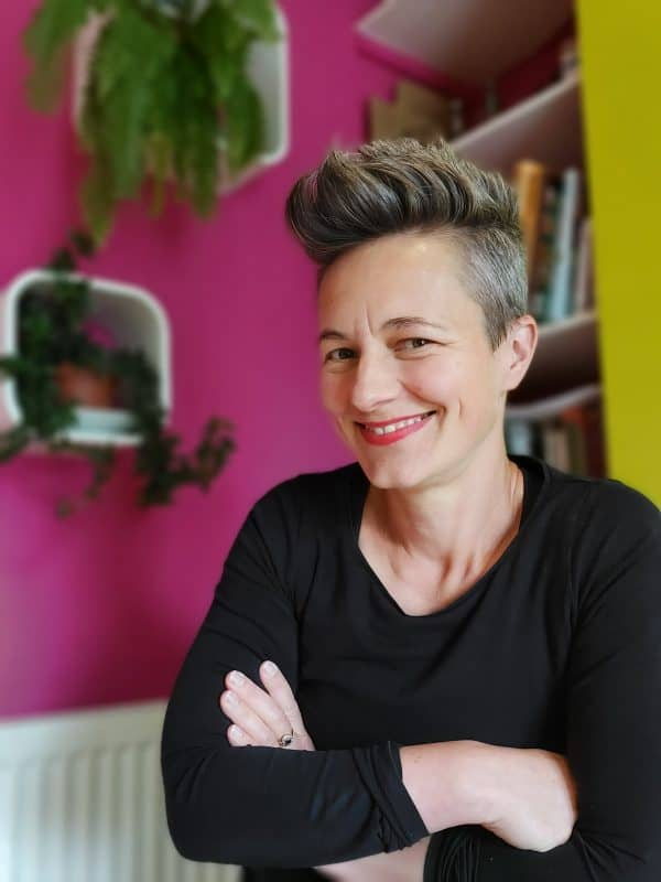 Anna Mapson smiling wearing a black long sleeved top against a pink wall with plants hanging in background