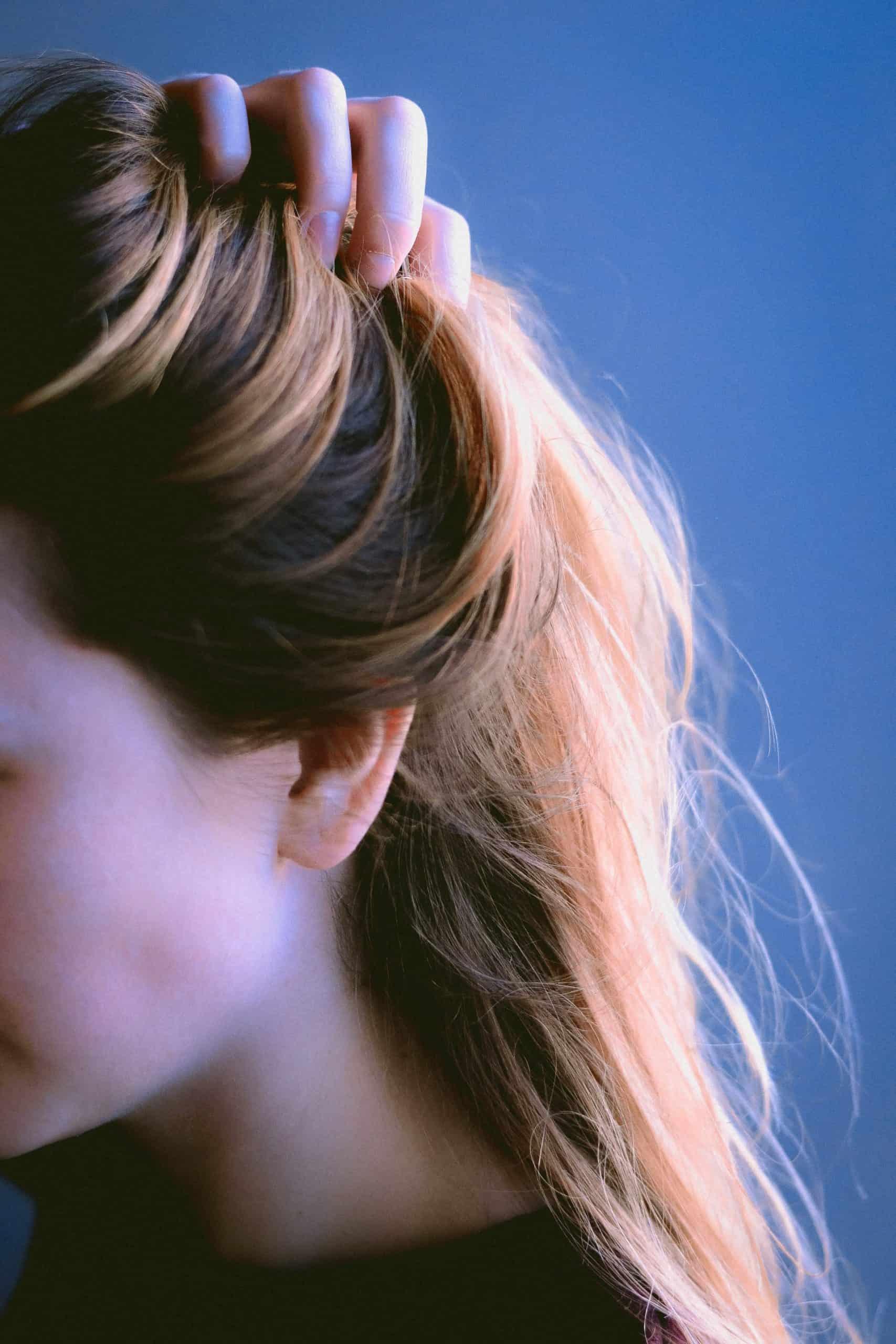 Woman close up lifting up her hair - IBS and hair loss