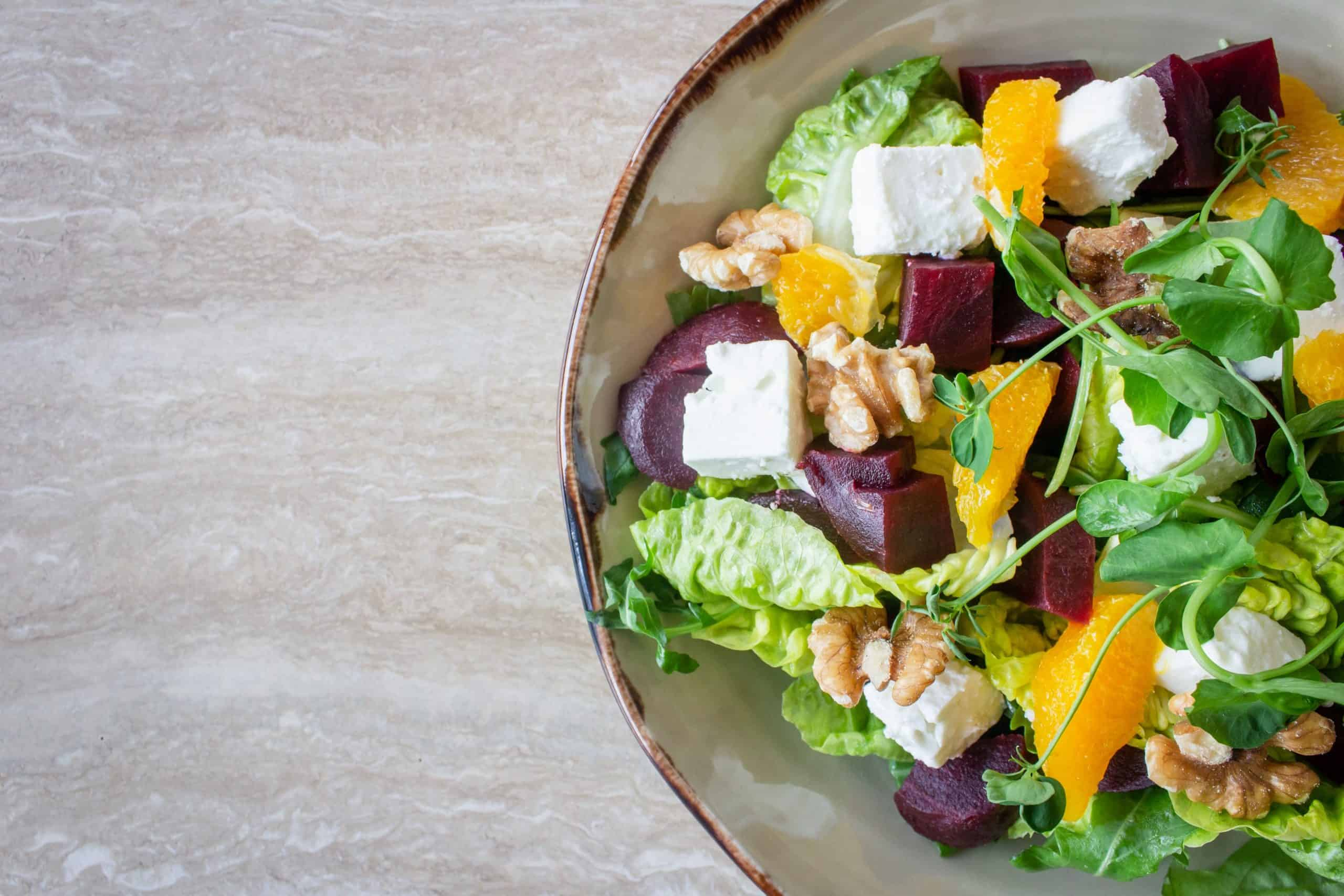 bowl of salad with feta cheese, yellow pepper and rocket. Round bowl against a grey wood background