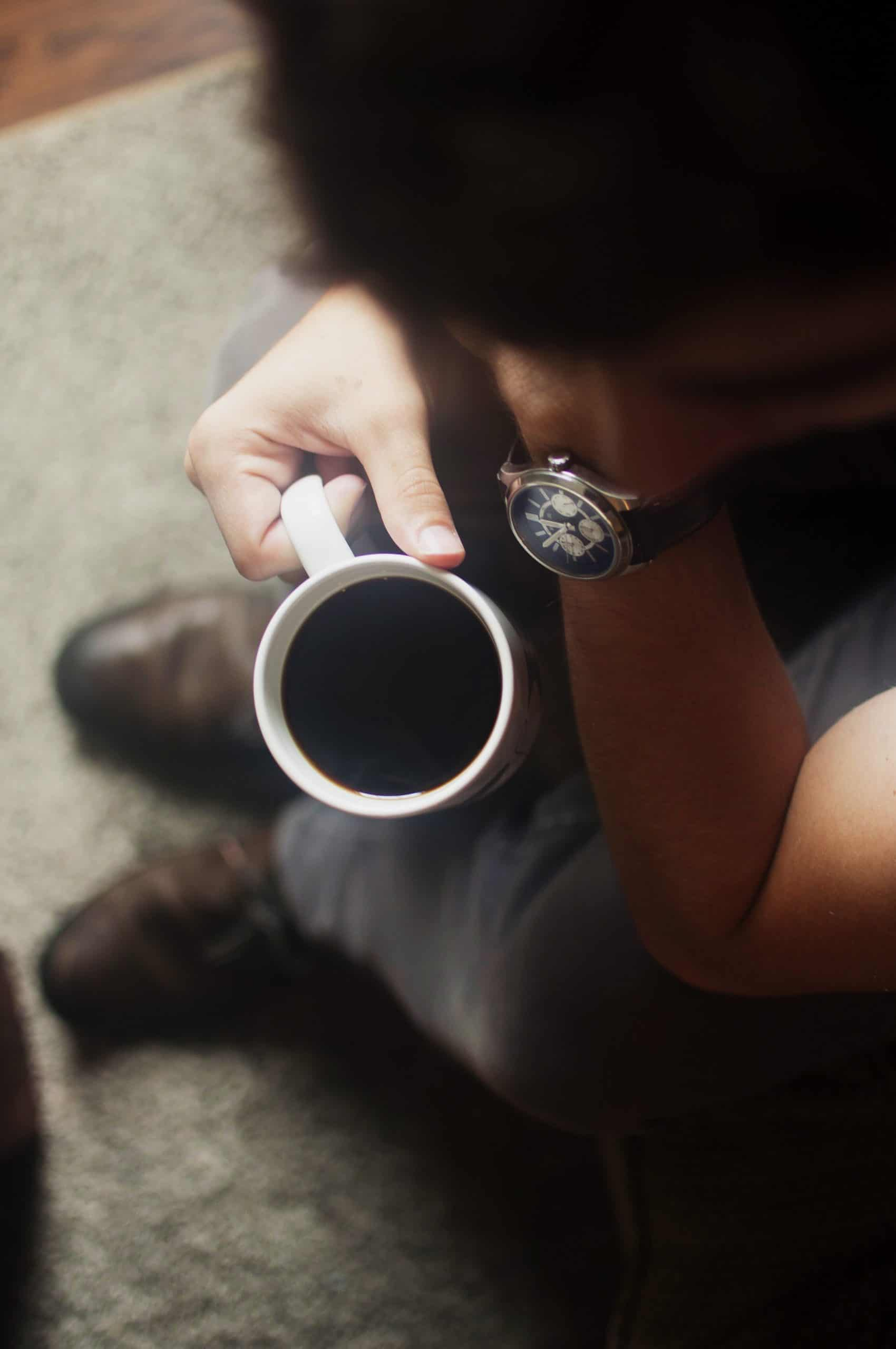 blurred person bending over a cup of black coffee