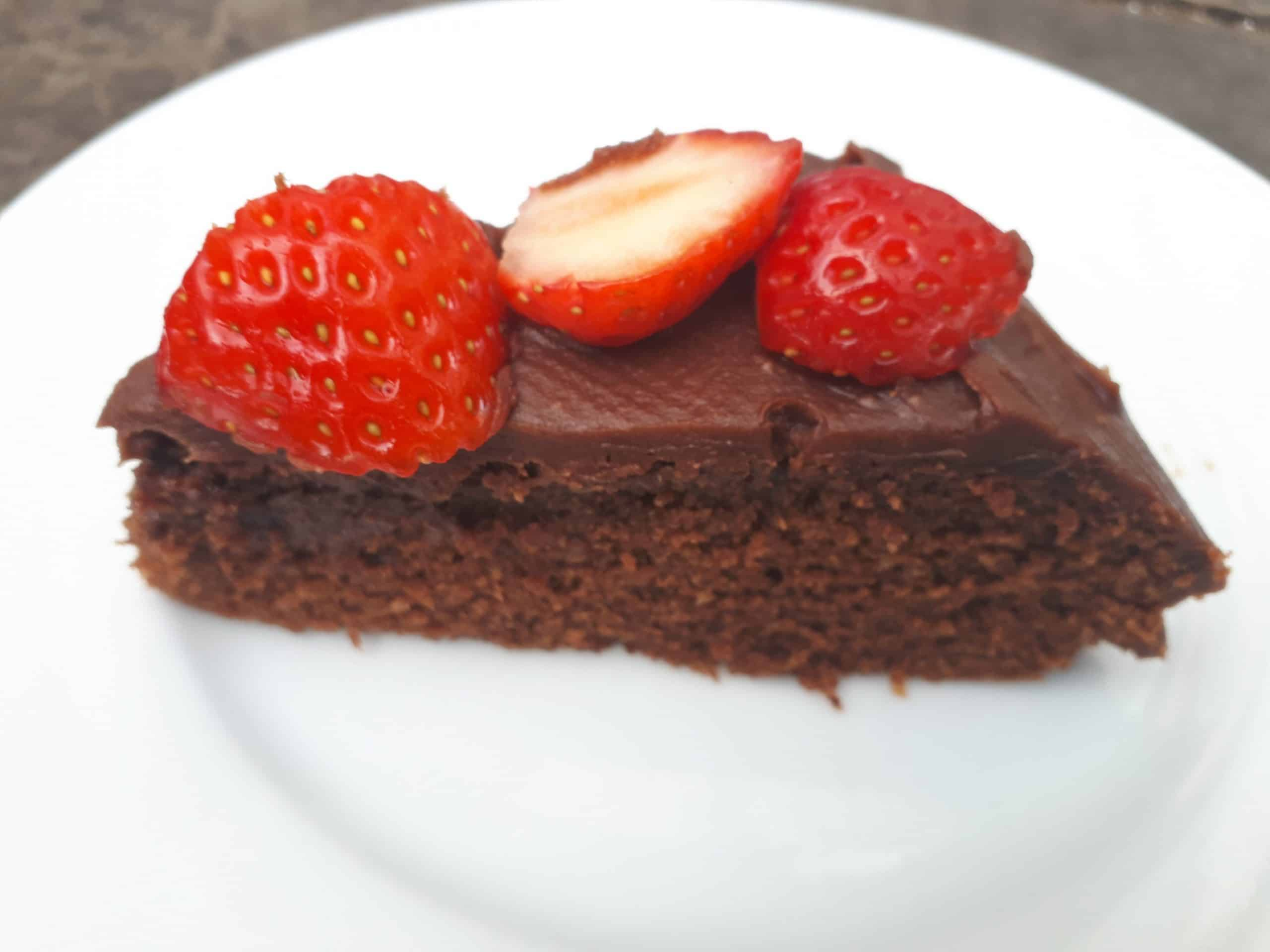 piece-of-chocolate-cake-strawberries-sliced-on-thick-icing - goodness-me-nutriton