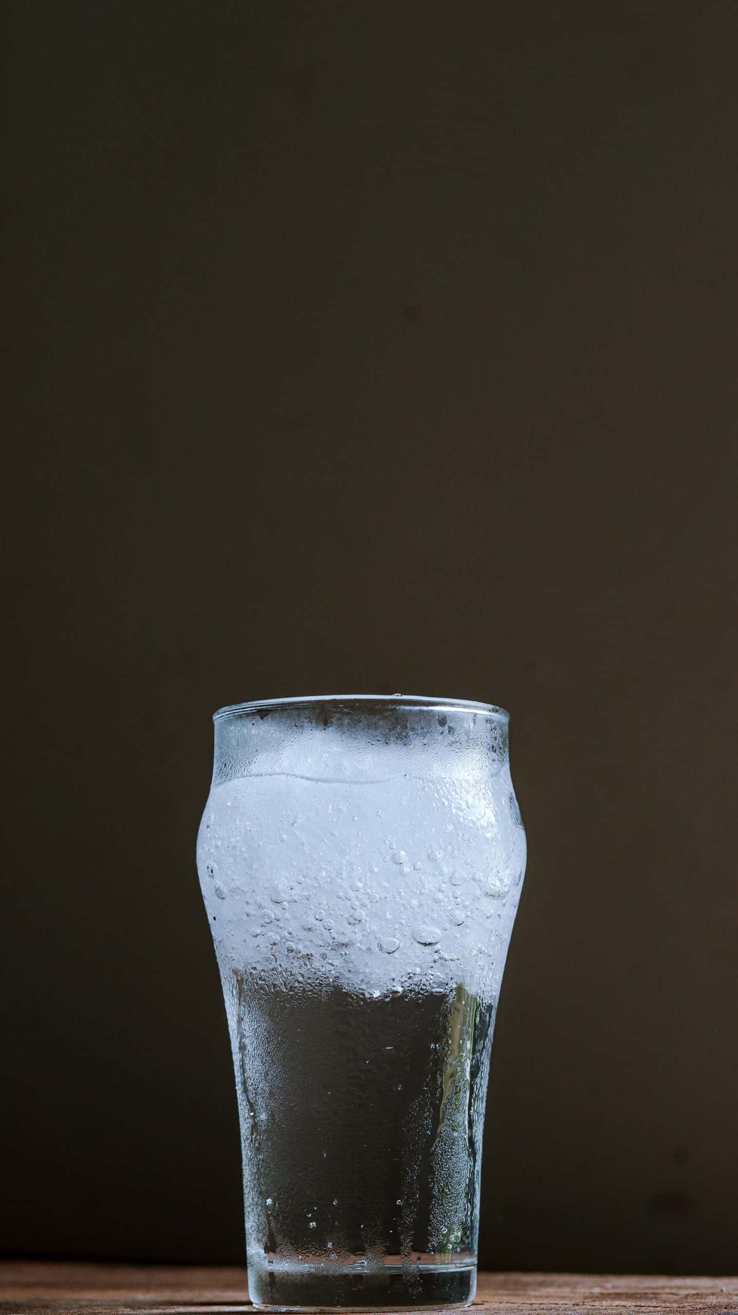 glass of water with ice, against a black background