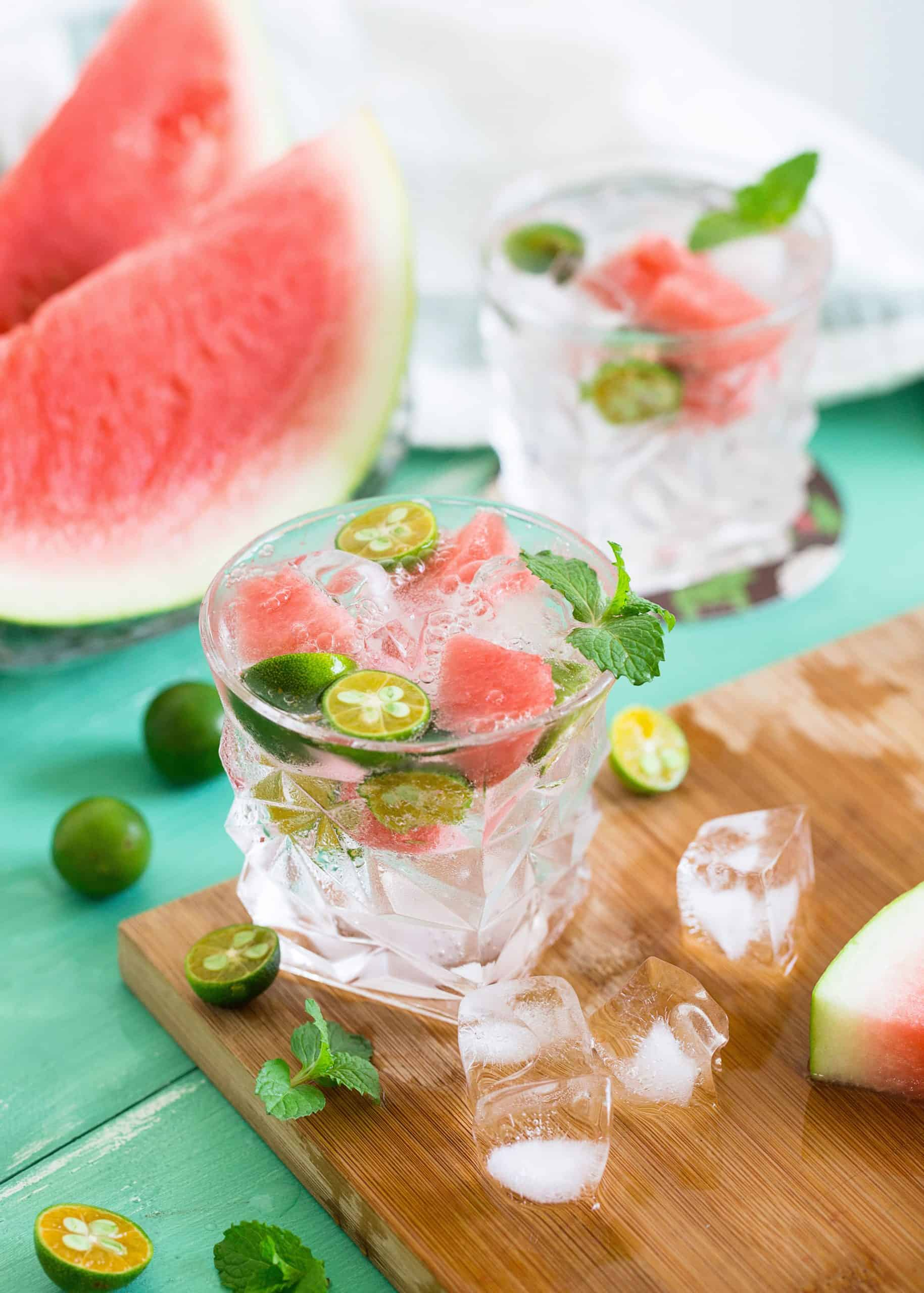 slices of watermelon, glass of water with ice and mint on a wooden board